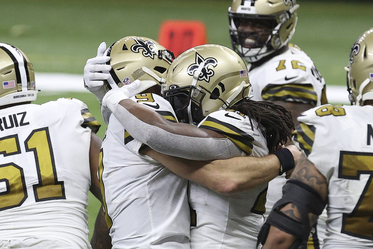 Drew Brees #9 and Alvin Kamara #41 of the New Orleans Saints embrace following a touchdown by Kamara during the fourth quarter against the Minnesota Vikings at Mercedes-Benz Superdome on December 25, 2020 in New Orleans, Louisiana.