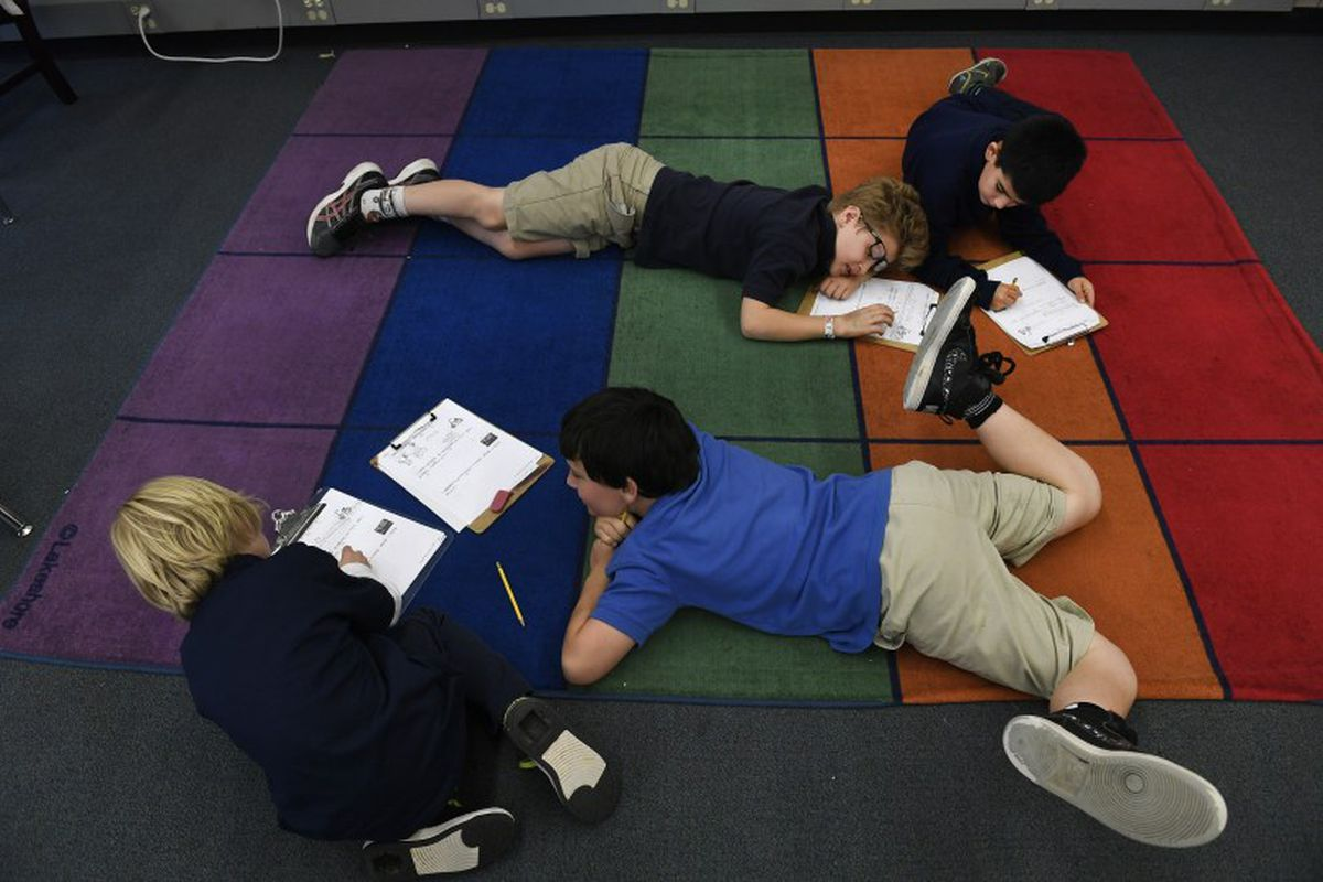 Third-grade students at the Denver Language School do schoolwork on the floor.