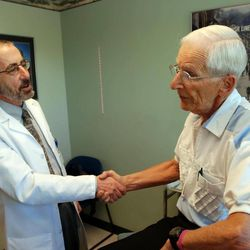In this June 19, 2012 photo, Dr. Bruce Stowell shakes hands with patient Robert Busch at his office in Grants Pass, Ore. Stowell is among many doctors in rural areas who have capped the numbers of Medicare patients they take due to low reimbursement levels. A nationwide shortage of primary care physicians willing to set up practice in rural areas is making the problem worse.