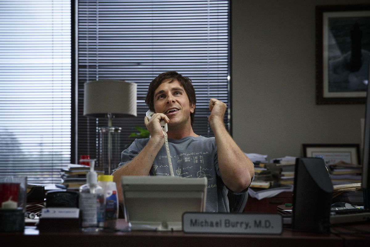 Michael Burry (Christian Bale) at his desk on the phone in The Big Short