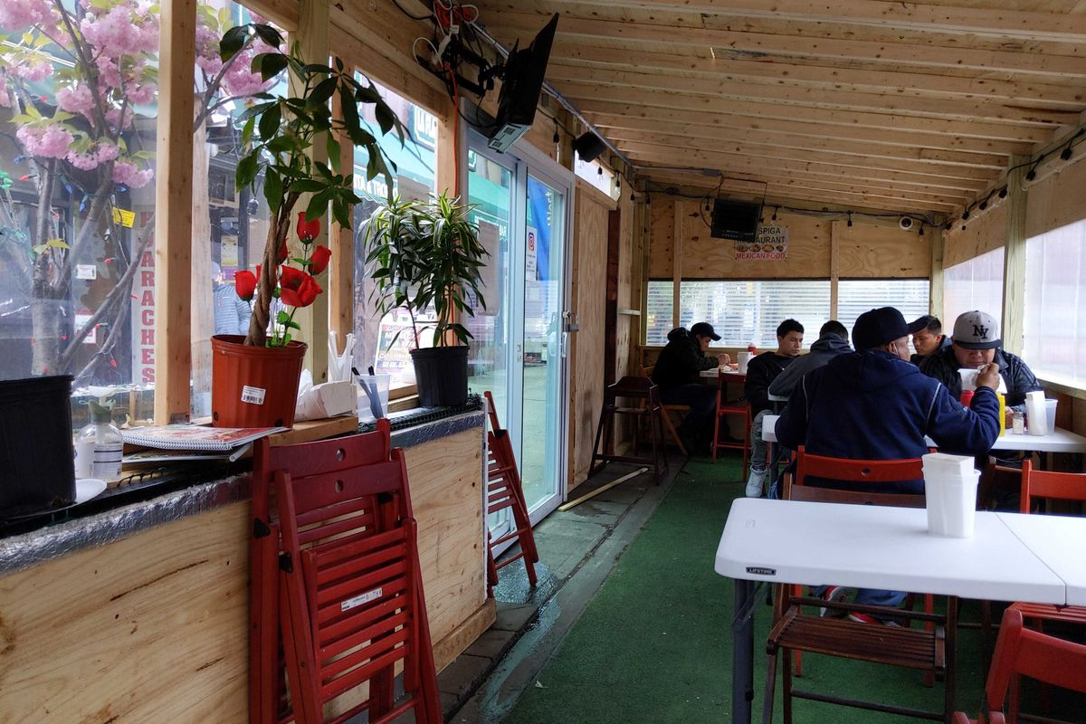 A handful of customers sit at plastic, fold-up tables inside of an enclosed outdoor dining structure