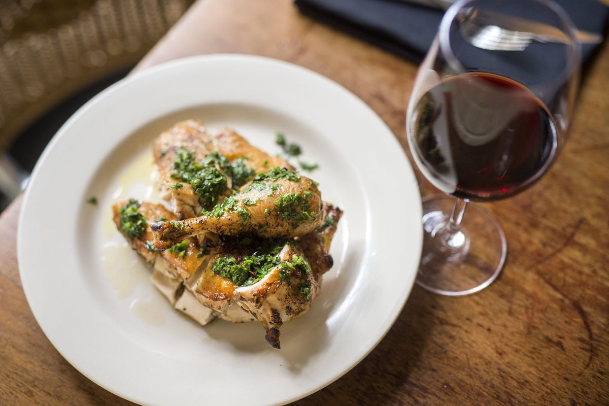A plate of roast chicken topped with salsa verde beside a glass of wine