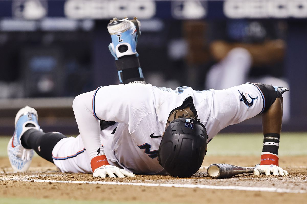 Lewis Brinson #25 of the Miami Marlins reacts after fouling a ball off of his foot in the third inning against the Atlanta Braves at loanDepot park