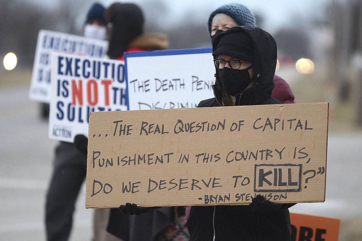 Christina Bollo of Urbana, Illinois, holds a sign as she protests the execution of Corey Johnson, near the Federal Correctional Complex, Thursday, Jan. 14, 2021, in Terre Haute, Ind.