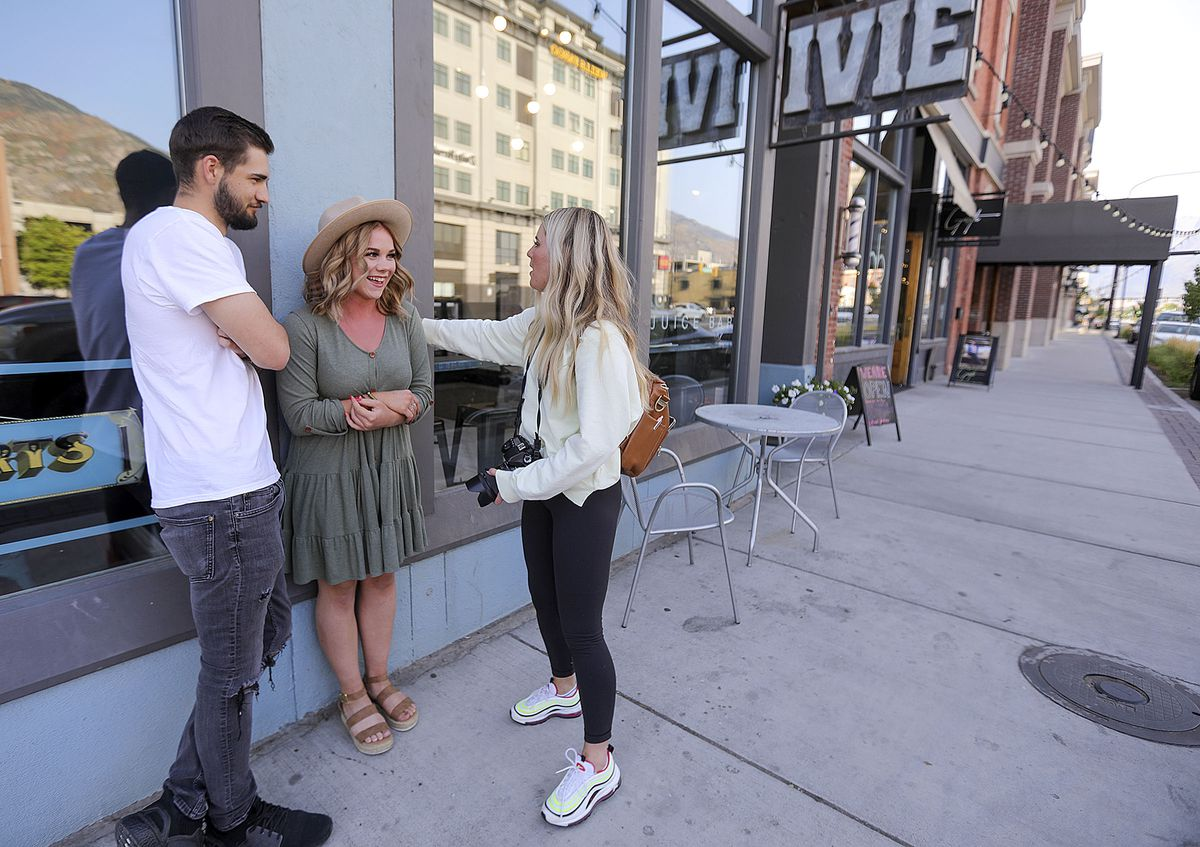 Photographer Sydnee Winegar, 19, right, poses Derek Powell, 21, and Nikki Webb, 19, for a photo shoot in downtown Provo on Monday, Sept. 14, 2020. The majority of recent COVID-19 cases are among people between the ages 14-24, many of them living in Utah County.
