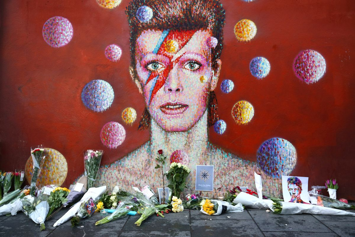 Flowers are laid beneath a mural of David Bowie in Brixton, England.