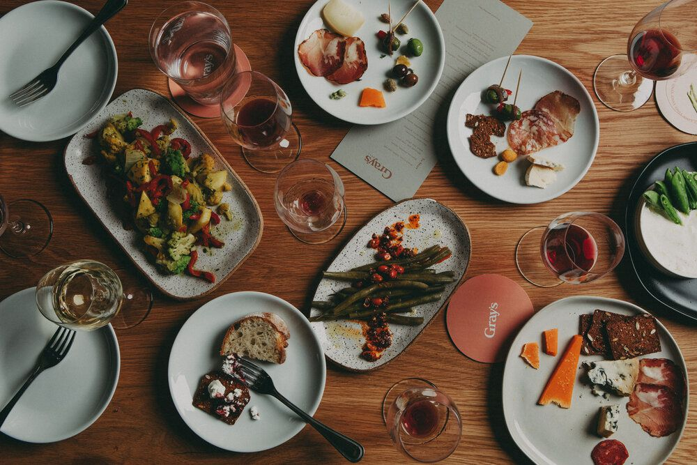 """Overhead view of a spread of small wine bar-style dishes and glasses of wine on a wooden table. Coasters read """"Gray's."""""""