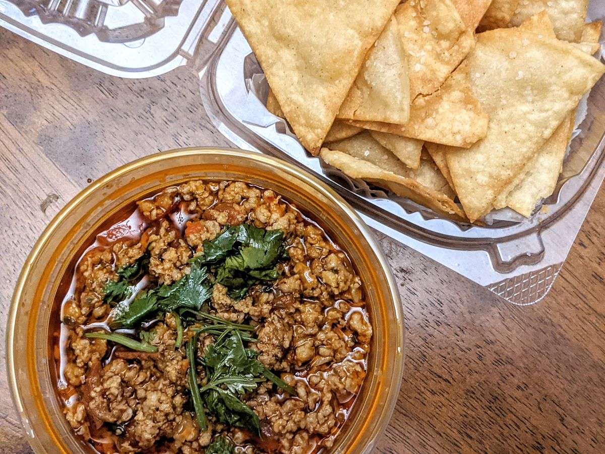 overhead view of a thick red dip with ground pork and a side of tortilla chips on a wooden table
