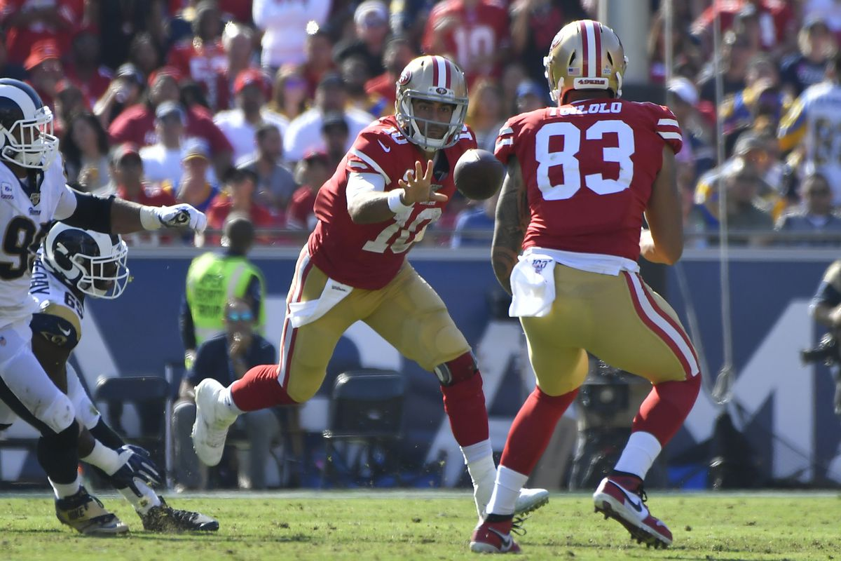 Jimmy Garoppolo of the San Francisco 49ers throws a shuffle pass to Levine Toilolo #83 in the third quarter against the Los Angeles Rams at Los Angeles Memorial Coliseum on October 13, 2019 in Los Angeles, California.