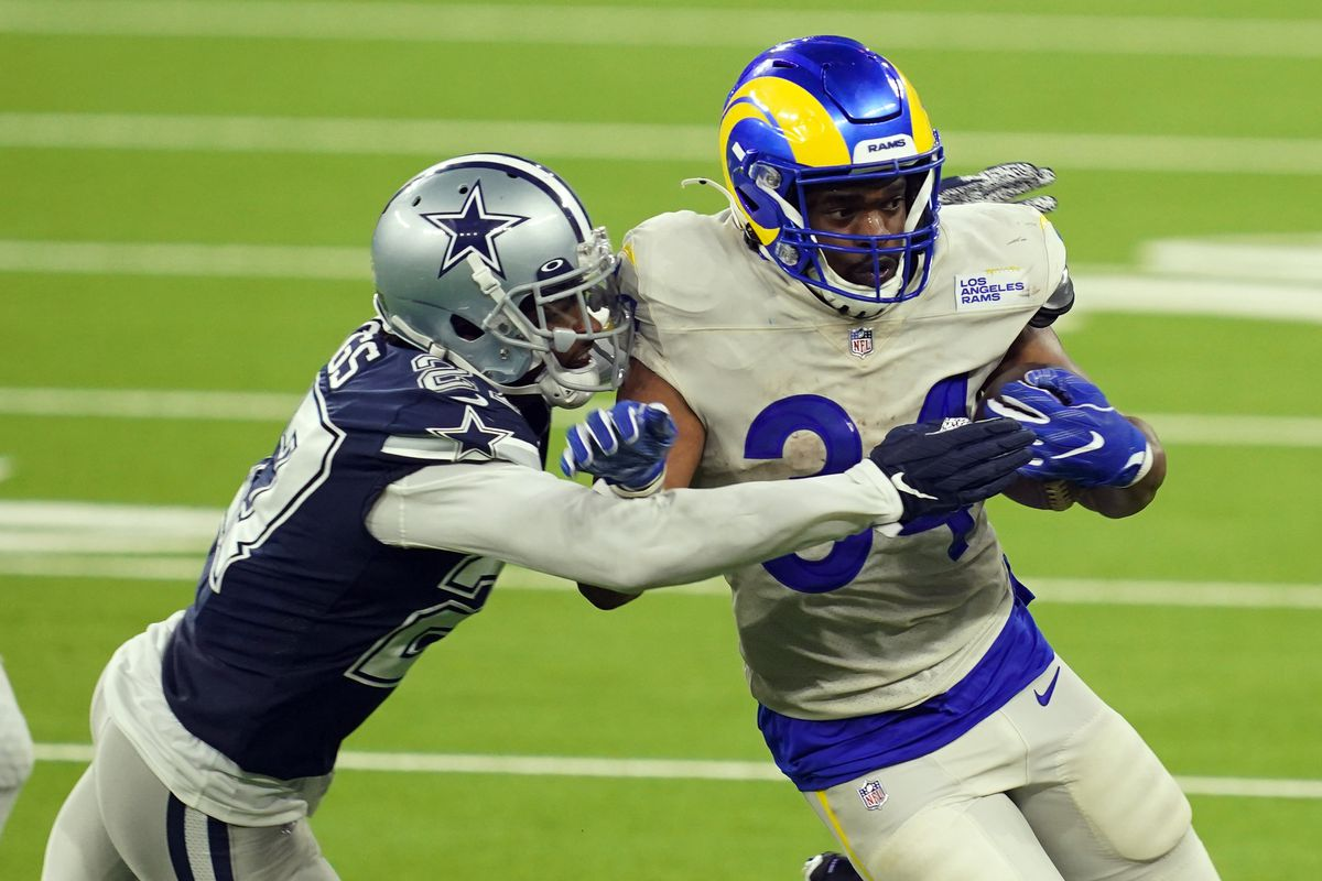 Los Angeles Rams running back Malcolm Brown is defended by Dallas Cowboys cornerback Trevon Diggs in the fourth quarter at SoFi Stadium. The Rams defeated the Cowoboys 20-17