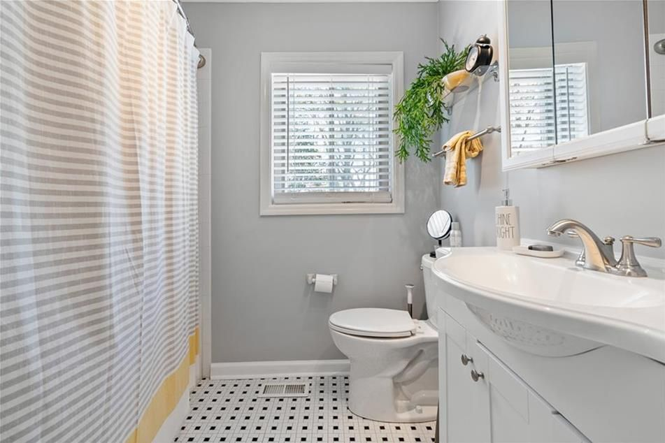 A sink at right and a shower at left in a bathroom.