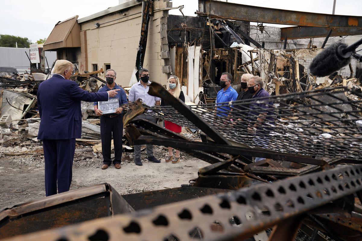 President Donald Trump talks to business owners on Tuesday, Sept. 1, 2020, in Kenosha, Wis., where he was touring an area damaged during demonstrations after a police officer shot Jacob Blake in Kenosha, Wis.