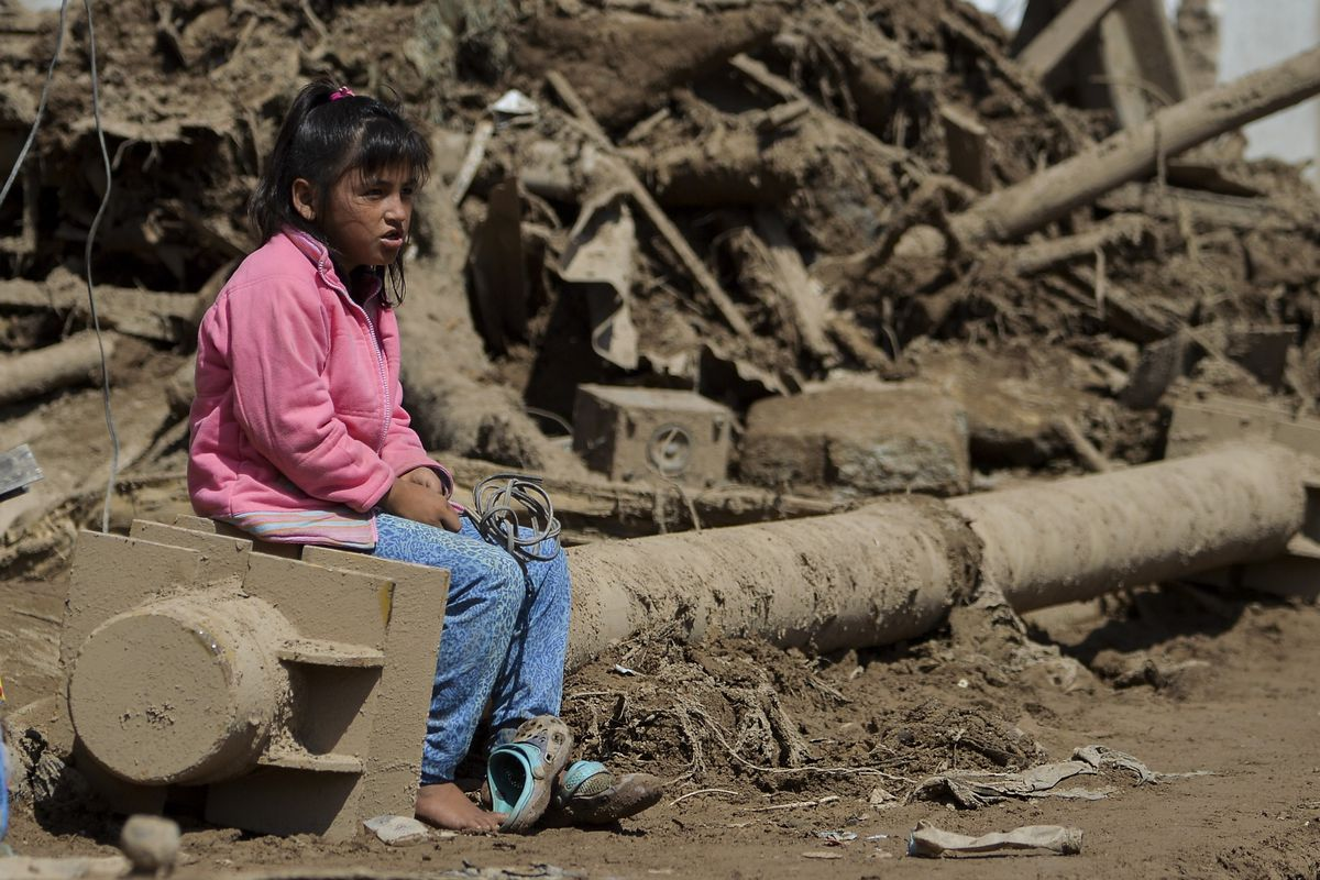 A girl sits amid rubble caused by flooding in Mocoa, Colombia, this month.