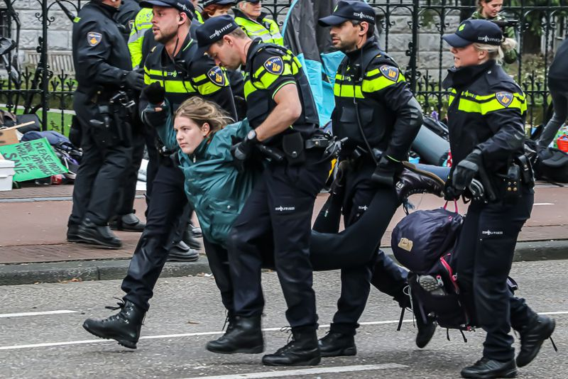 A protester is carried off by several police officers at a climate change protest in Amsterdam.