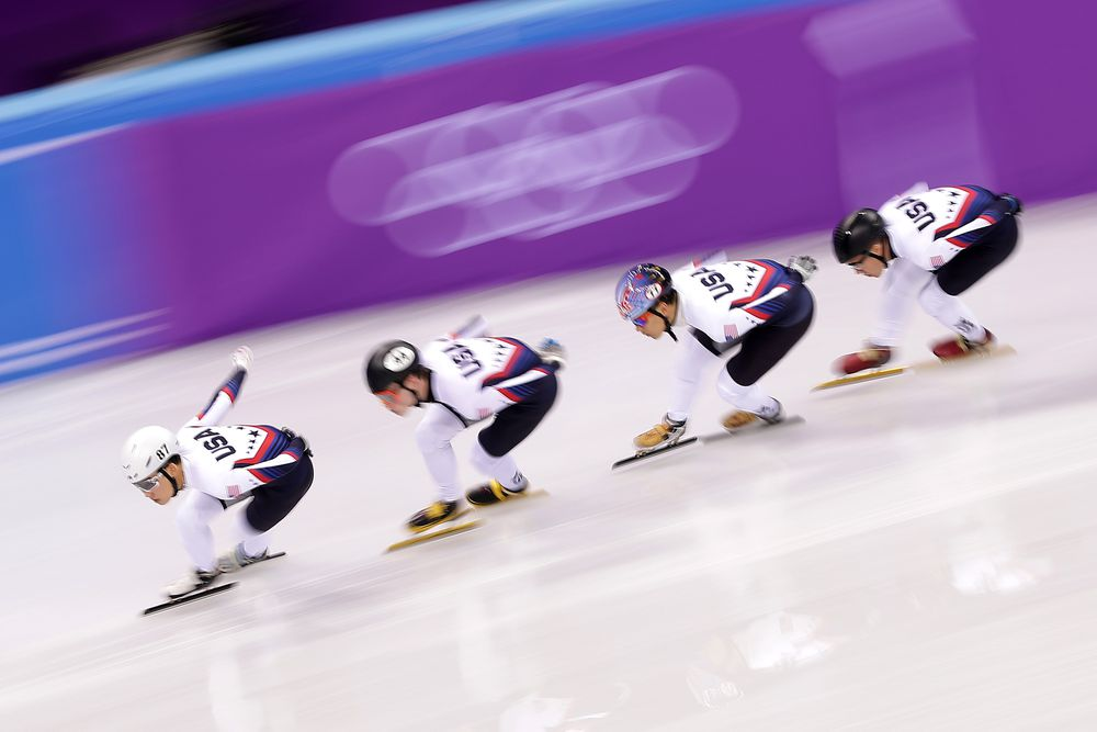 Four Olympic speed skaters in USA jerseys racing on the ice