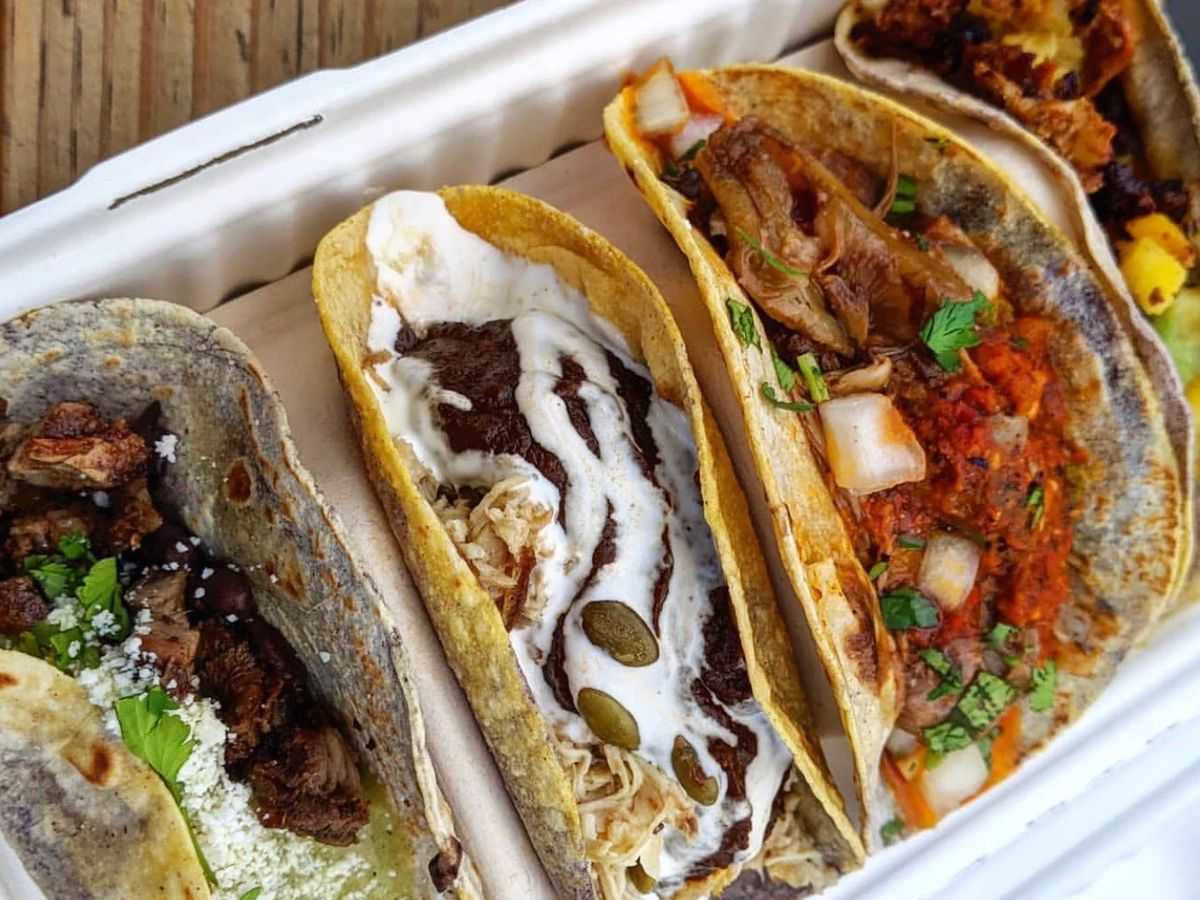Four tacos in a cardboard takeout container