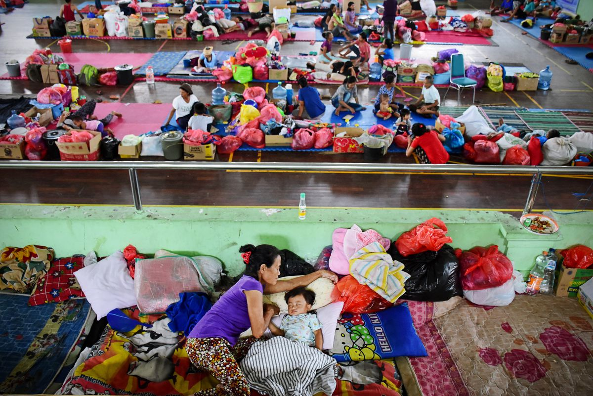 A mother is putting her child to sleep at Gunung Agung Refugee Post, Sweca Pura Sports Arena, Klungkung, Bali on Thursday, November 23, 2017. After a phreatic eruption on Tuesday 21 November, the number of refugees at Sweca Pura Sports Arena post amounted to 2,966 people. Mount Agung erupted phreatically by releasing thick gray smoke and ash with medium pressure with a height of 700 meters from the top of the crater. The day before the eruption, the total number of refugees reached 29,184 people spread over 278 dots. Refugees increased 60 souls to 29,245 people after the eruption with the same point of distribution. Two days after the eruption, the number of refugees was significantly reduced to 3,248 people to 25,997 people spread over 229 refugee points. (Photo by Keyza Widiatmika/NurPhoto via Getty Images)