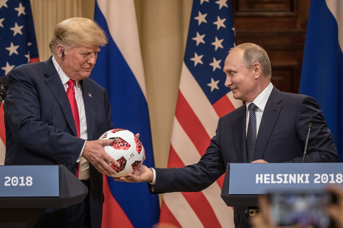 Russian President Vladimir Putin hands US President Donald Trump a World Cup soccer ball during a joint press conference after their summit on July 16, 2018 in Helsinki, Finland.