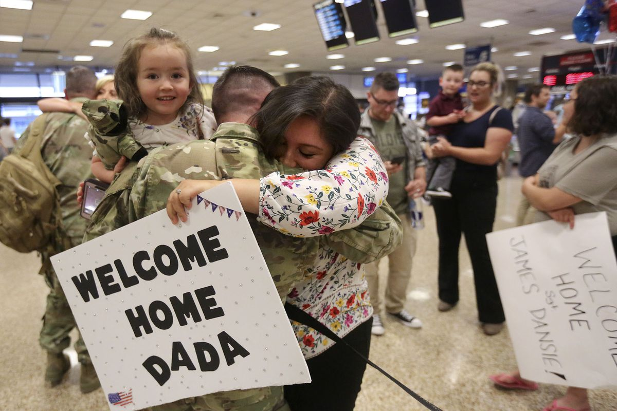 First Lt. Taylor Duke holds his daughter Leslee Duke and hugs his wife Amanda Duke at the Salt Lake International Airport in Salt Lake City on Tuesday, Aug. 27, 2019, as he and other members of the Utah National Guard's 4th Infantry Division Main Command Post Operational Detachment return home after serving in Afghanistan for 10 months in support of Operation Freedom's Sentinel.
