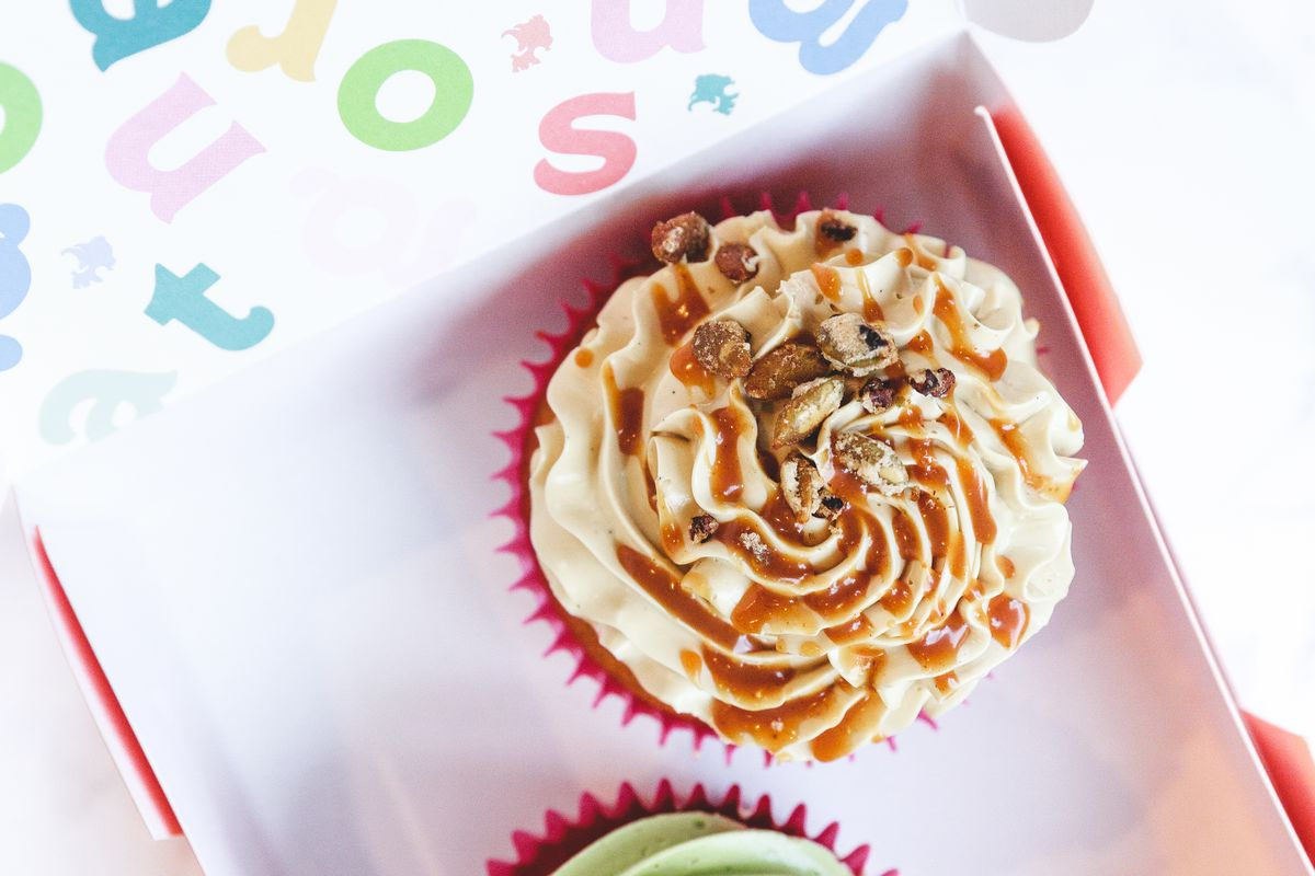 A cupcake topped with frosting and sauce inside a box.