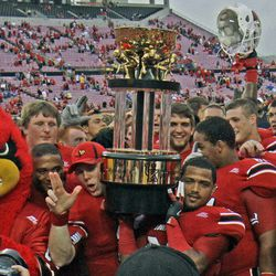 Louisville players celebrate with the Governor's Cup trophy after defeating Kentucky 32-14 in an NCAA college football game at Cardinal Stadium in Louisville, Ky., Sunday, Sept. 2, 2012.
