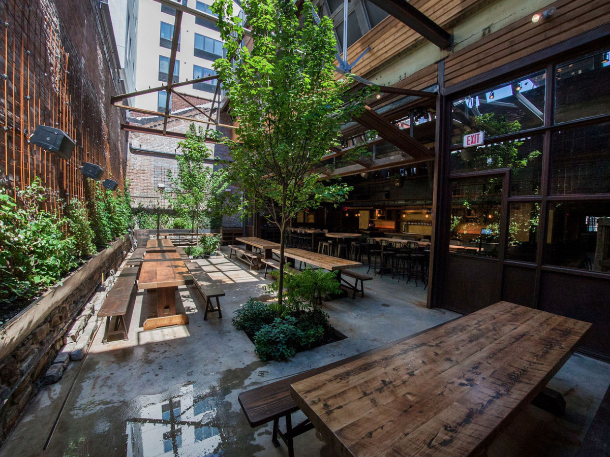 The backyard of a restaurant with benches, chairs and greenery