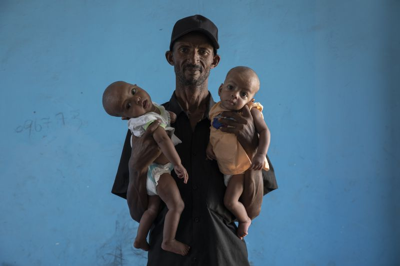 Tigrayan refugee Abraha Kinfe Gebremariam, 40, holds his 4-month-old twin daughters Aden (left) and Turfu.