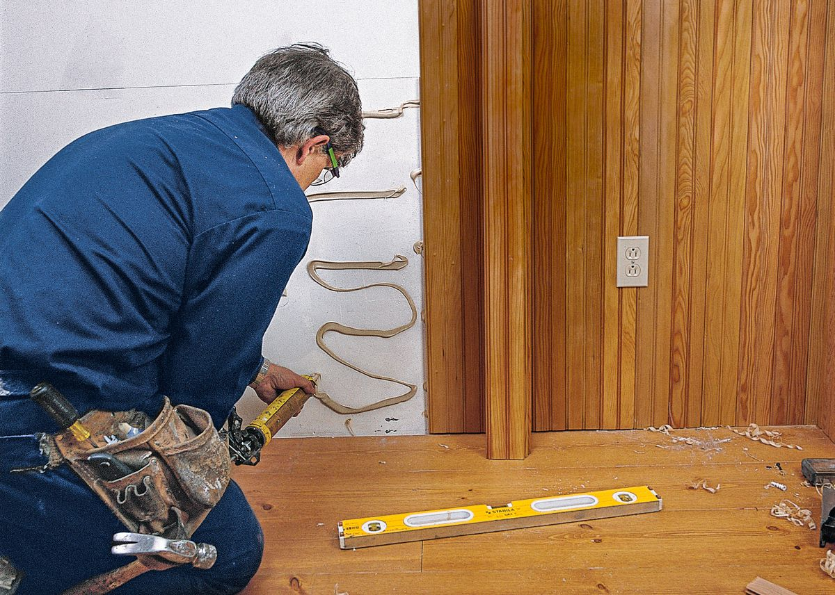 Man Applies Adhesive To Wall For Paneling