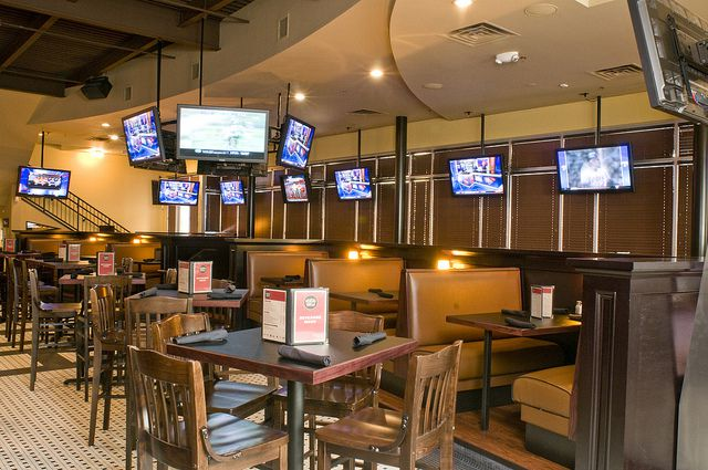The interior of a bar. There are booths, tables, and chairs. There are television monitors hanging from the ceiling above the tables.