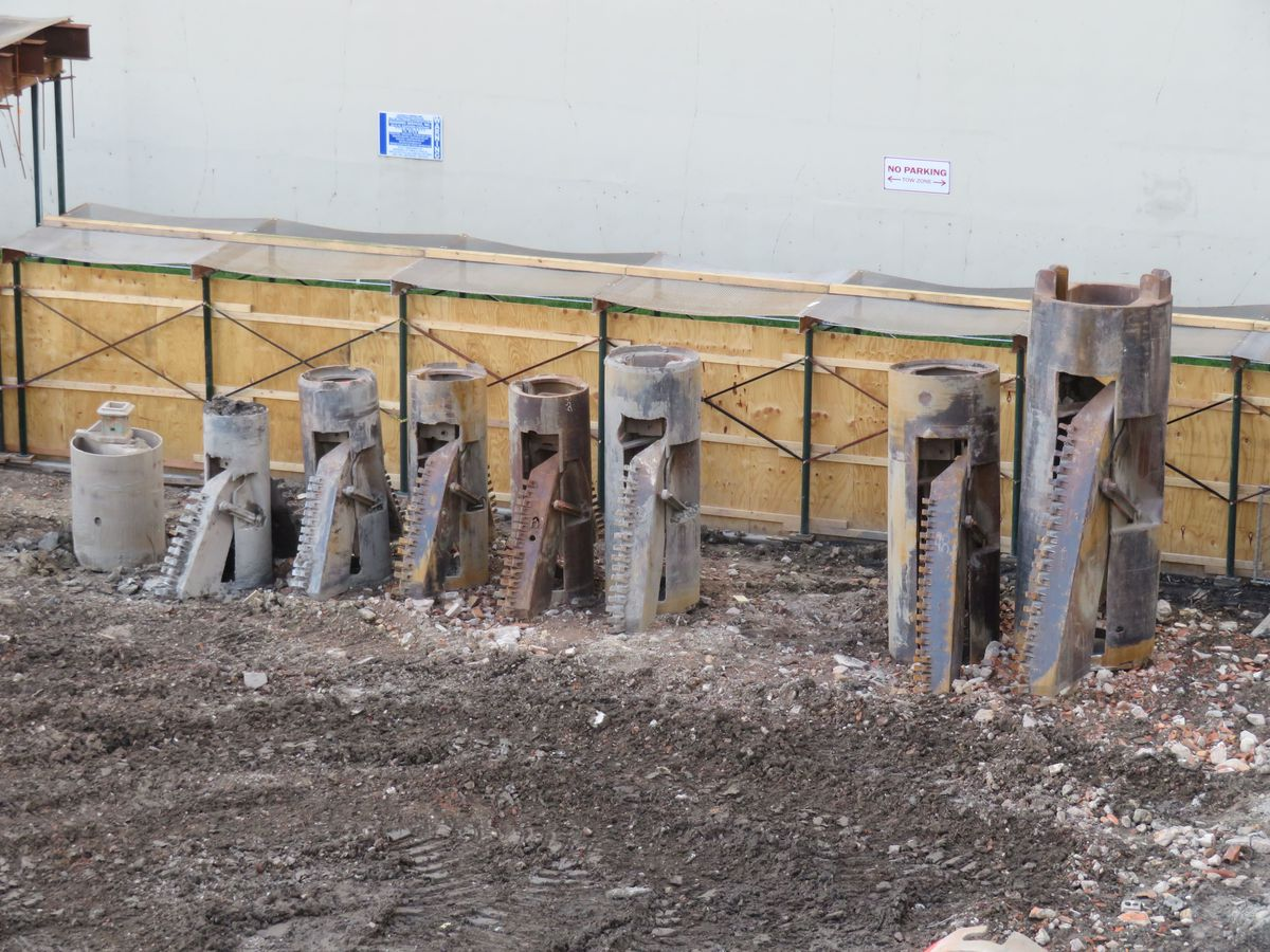 A line-up of different sized drilling heads next to a wooden construction fence.