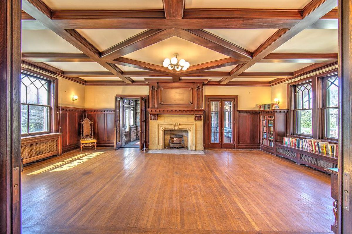Interior of great room with box beam ceilings and wood paneling, shelves, and doors done in rich wood. There's a fireplace and hardwood floors.
