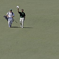 Louis Oosthuizen, of South Africa, and his caddie Wynand Stander react after Oosthuizen's double eagle two on the par 5 second hole during the fourth round of the Masters golf tournament Sunday, April 8, 2012, in Augusta, Ga.
