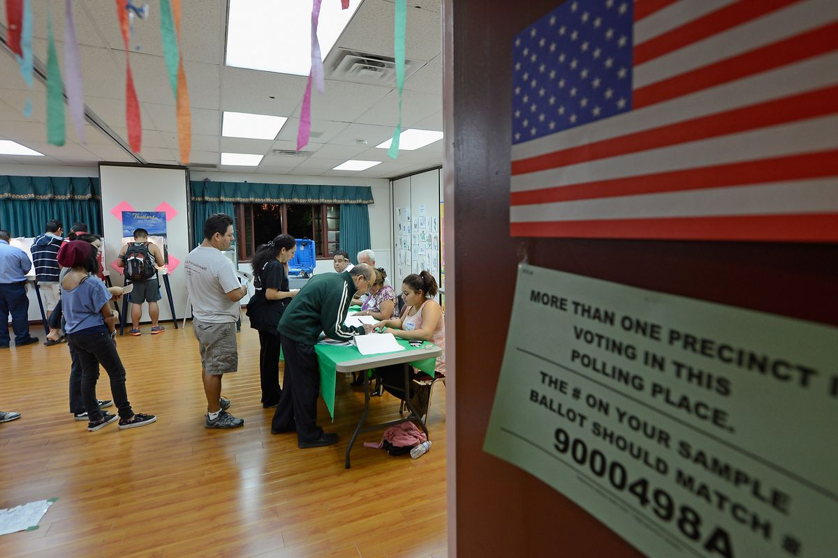People wait in line to pick up their ballots in the US presidential elections in the polling place at Wat Thai Temple on November 6, 2012 in Los Angeles.