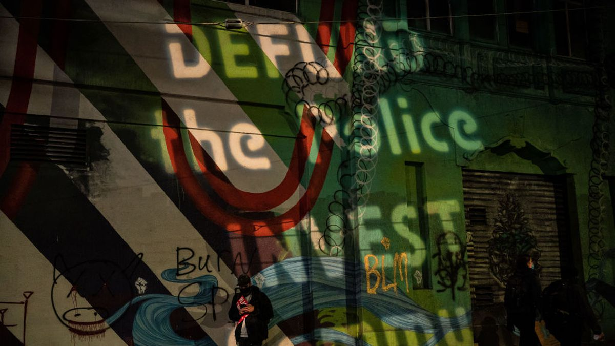 """A lighted message on a Seattle wall at night says """"Defund the police, invest in community"""""""