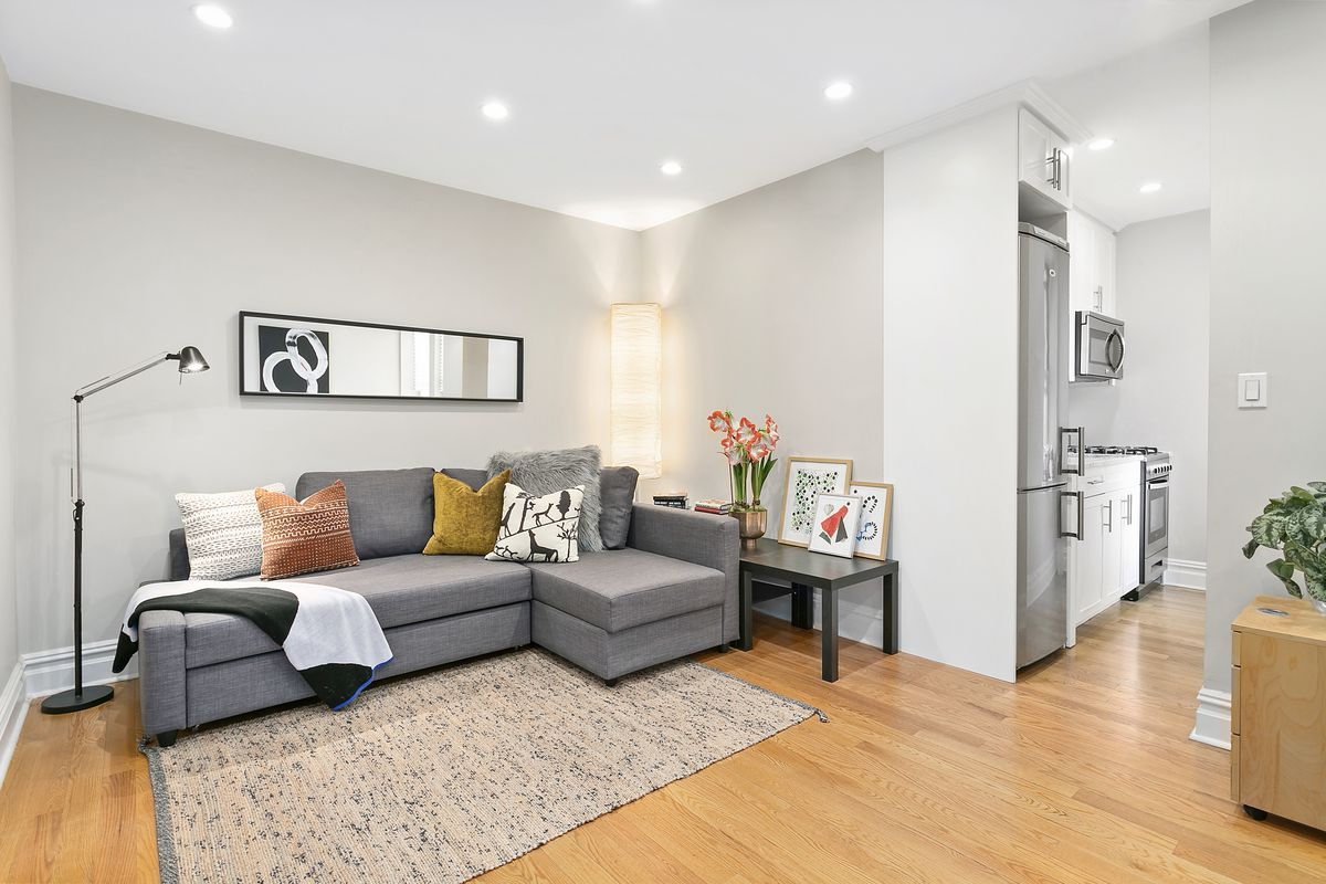 A living room with a grey couch, a rug, hardwood floors, and grey and white walls.