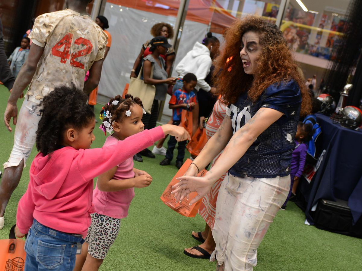 Kids receive candy from a zombie dressed as a football player.