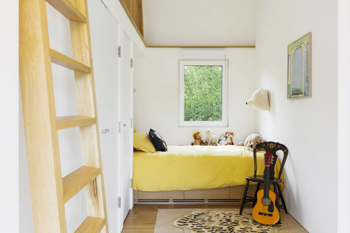 A narrow bedroom with a window, yellow bed, and ladder to a mezzanine level.