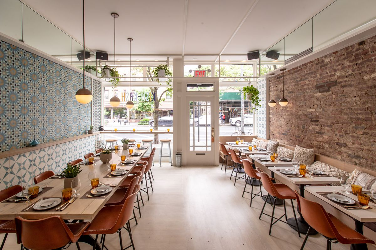 The interiors of a restaurant with rows of tables and chairs on either side, low-hanging lights, and the glass front door can be seen in the distance