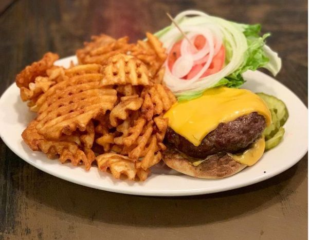 A cheeseburger with exposed top and waffle fries on the side.