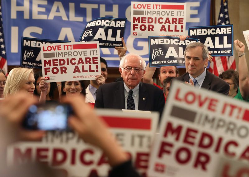 Senator Bernie Sanders onstage surrounded by people waving Medicare-for-All signs.