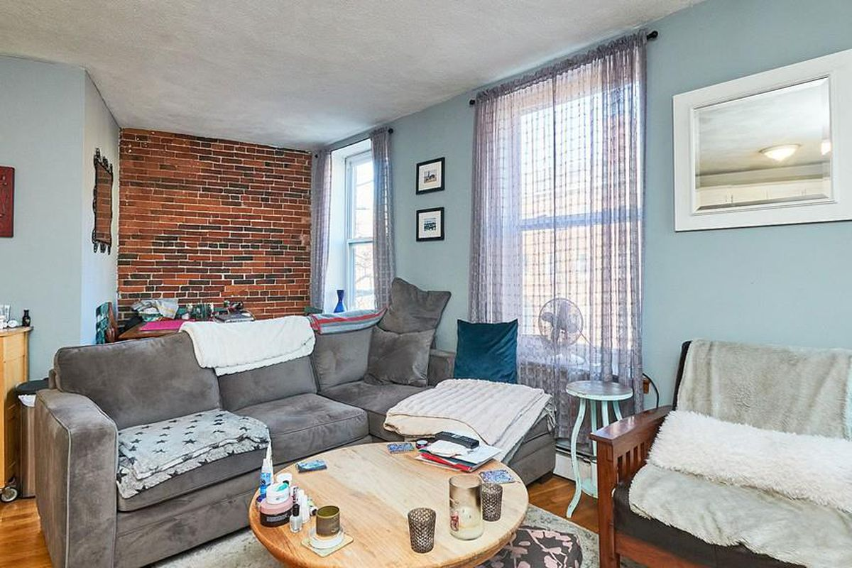 A living room with furniture, two windows, and a short wall of exposed brick.