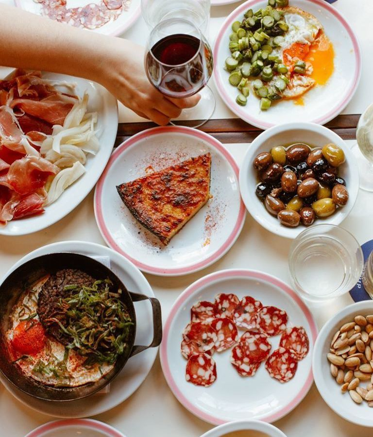 From above, a table filled with dishes, including charcuterie, olives, nuts, and Spanish tortilla