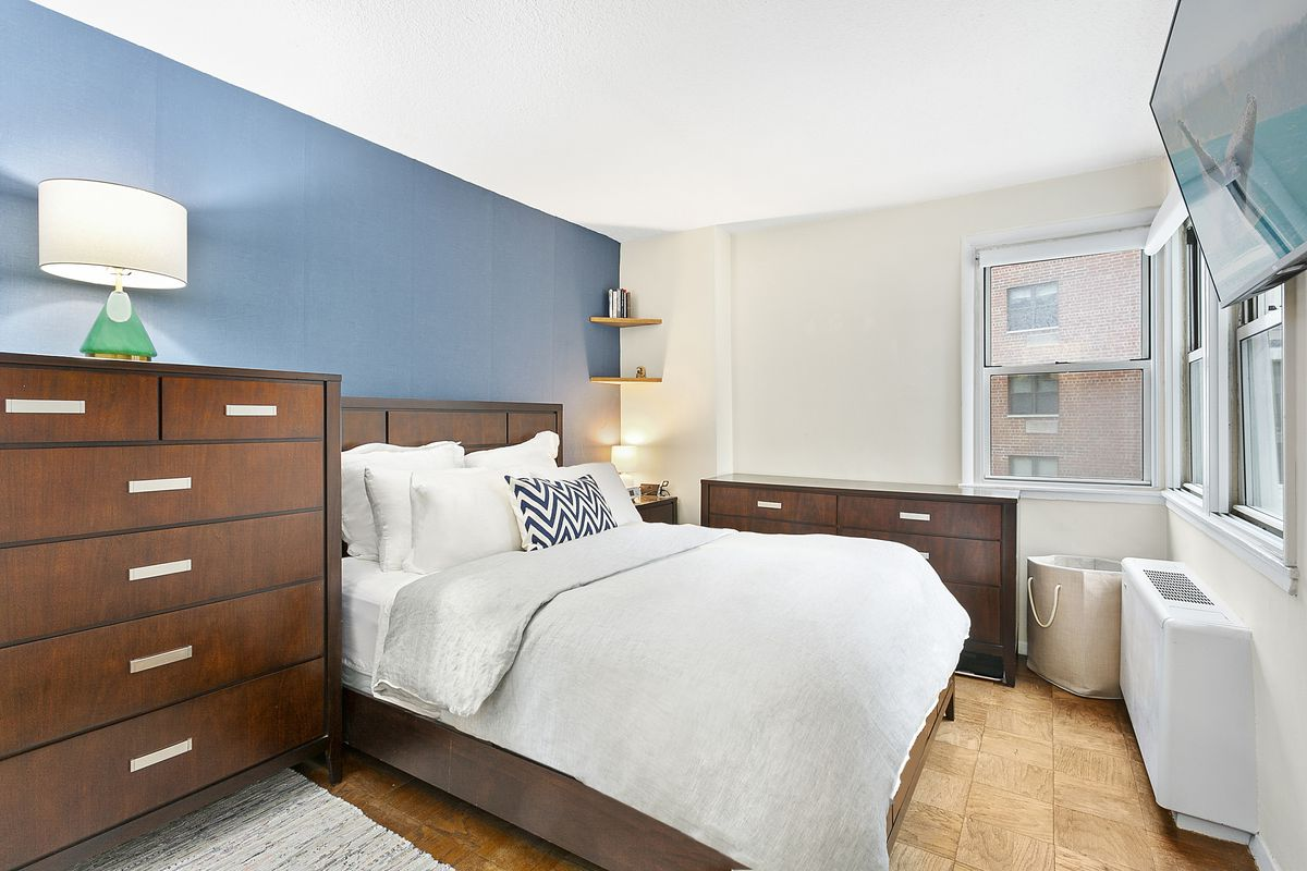 A bedroom with a large bed, hardwood floors, and wooden furniture.
