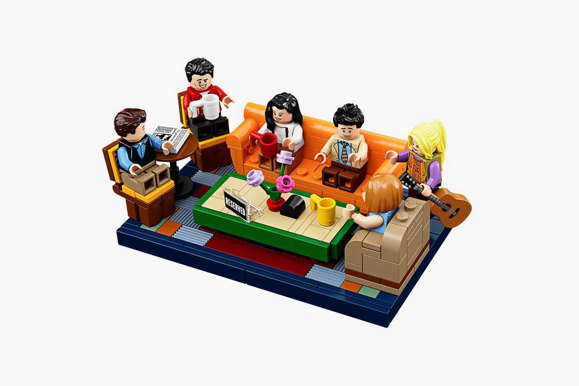 Lego people sitting on an orange Lego couch.