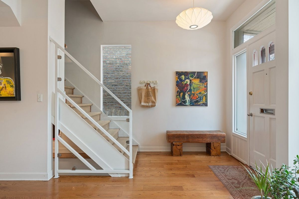 An entryway with a staircase, a painting, a paper light, and hardwood floors.