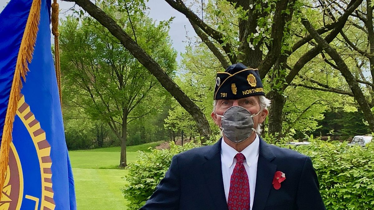 A man in a blue suit, military style cap, and mask holds an American Legion flag.