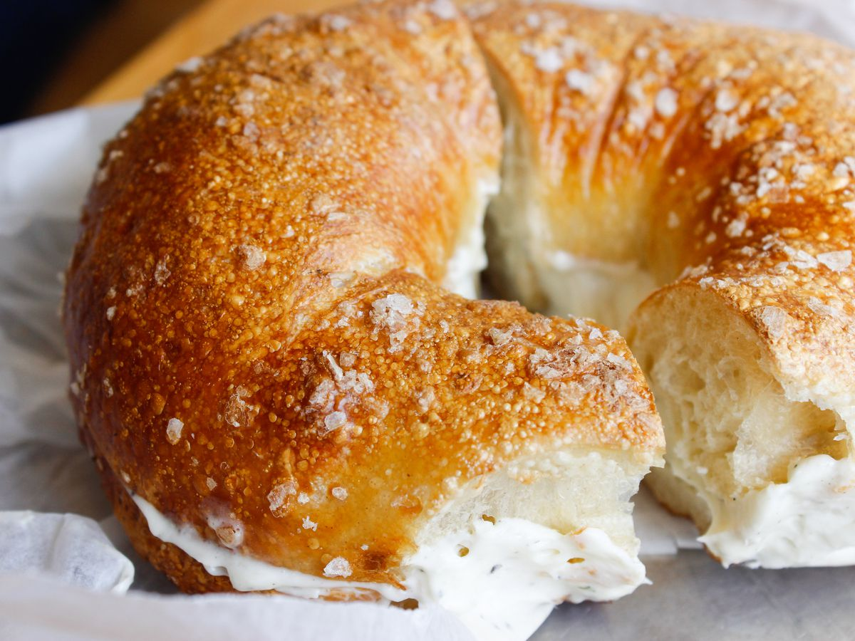 A close-up of a bagel with cream cheese, sliced in half