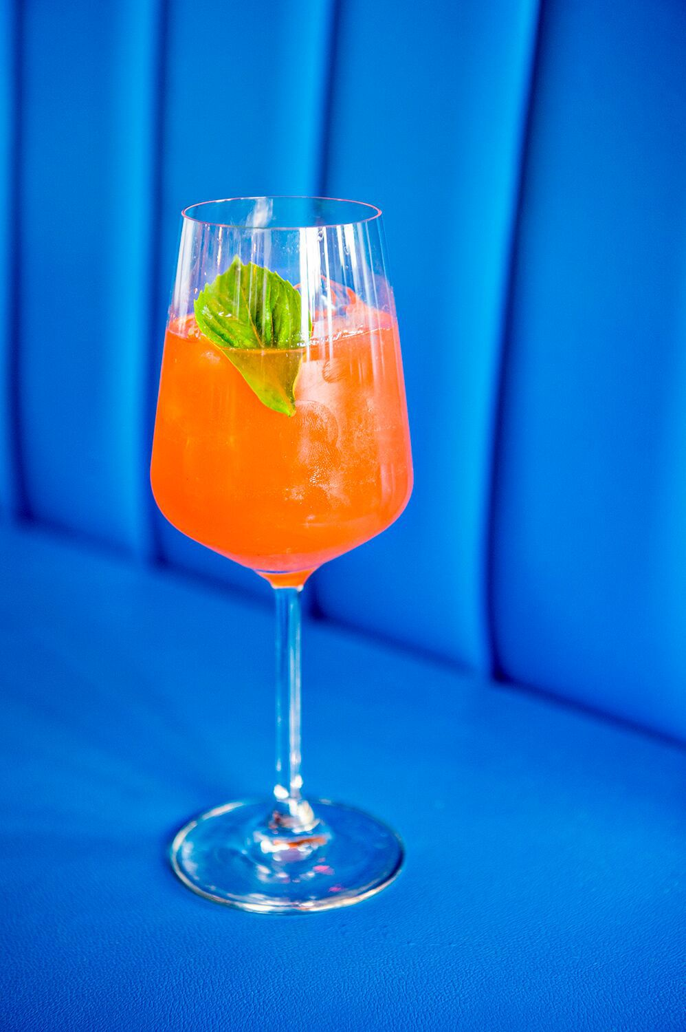 An orange cocktail in a wine glass