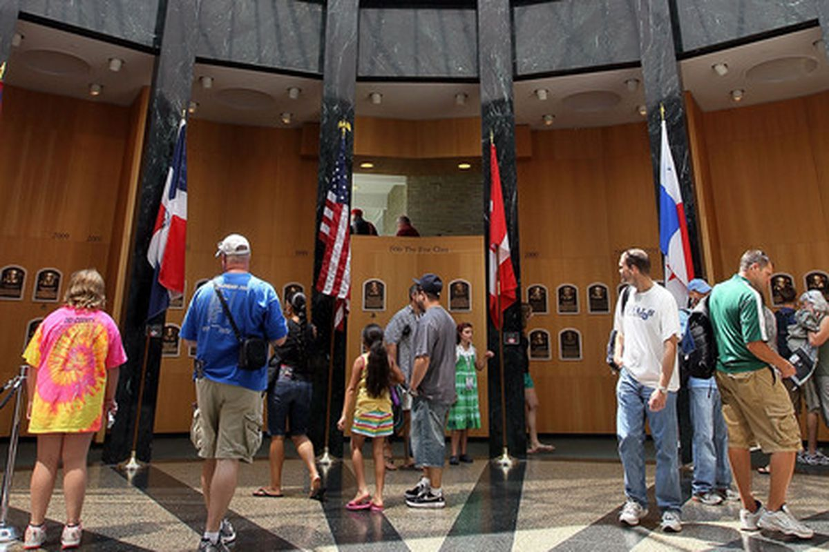 Patrons of the Baseball Hall of Fame and Museum view the plaques of inducted members during induction weekend on July 24 2010 in Cooperstown New York.