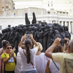 """People take photos of Timothy P. Schmalz's sculpture on the theme of refugees and migration, """"Angels Unawares,"""" that was unveiled on the occasion of the Migrant and Refugee World Day, in St. Peter's Square, at the Vatican, Sunday, Sept. 29, 2019."""